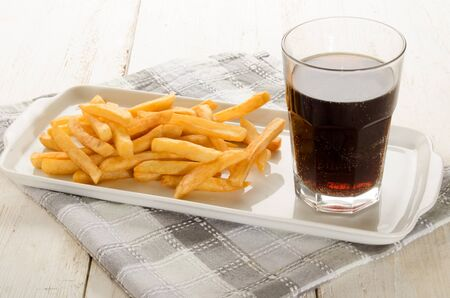 caffeinated: french fries on a porcelain plate and caffeinated brown soft drink Stock Photo