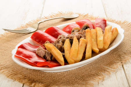 red bell pepper: french fries with minced meat and red bell pepper on oval plate