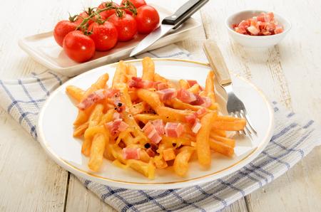 pancetta cubetti: affumicato cubetti di pancetta e patatine fritte marrone dorato con formaggio fuso su un piatto bianco