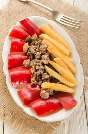 french fries plate: french fries with minced meat and red bell pepper on oval plate