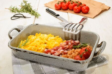 pancetta cubetti: british breakfast with scrambled eggs in a roasting tin, smoked bacon cubes, baked beans, fresh tomatoes, rosemary Archivio Fotografico