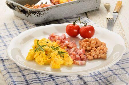 pancetta cubetti: prima colazione inglese con uova strapazzate su un piatto, cubetti di pancetta affumicata, fagioli, pomodori freschi, rosmarino Archivio Fotografico