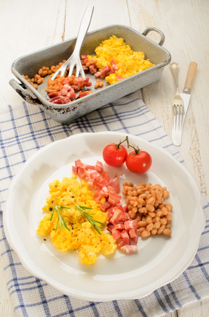 pancetta cubetti: british breakfast with scrambled eggs on a plate, smoked bacon cubes, baked beans, fresh tomatoes, rosemary