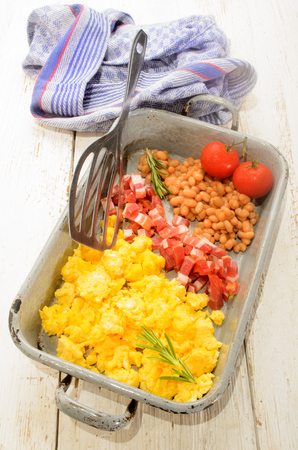 bacon baked beans: british breakfast with scrambled eggs in a roasting tin, smoked bacon cubes, baked beans, fresh tomatoes, rosemary Stock Photo