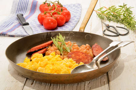 kitchen spanish: spanish breakfast with scrambled eggs in a brass pan, chorizo, baked beans, fresh tomatoes on a kitchen towel, rosemary and herbal scissor