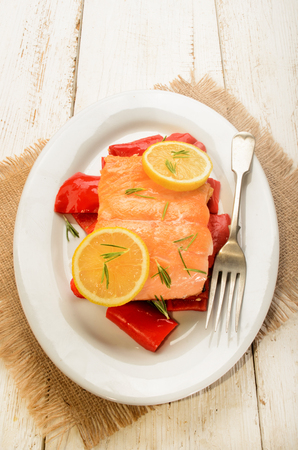 salmon filet: roasted salmon filet on red paprika, with lemon and rosemary on oval plate Stock Photo