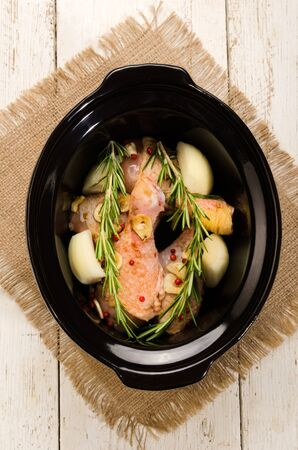 slow cooker: marinated chicken drumstick with red peppers, onion, garlic and rosemary in a black slow cooker