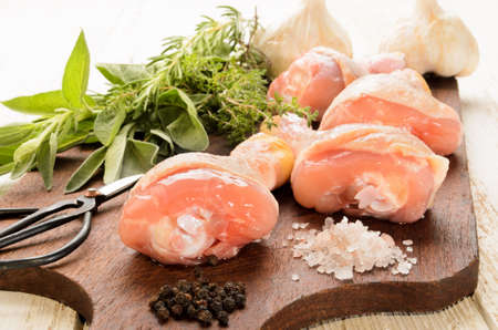 drumsticks: raw chicken drumsticks fresh herbs from the garden, coarse sea salt and peppercorns on a wooden board