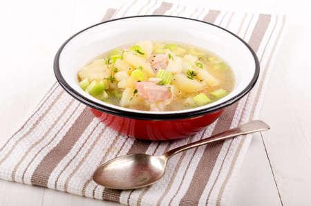 pancetta cubetti: zuppa di verdure caldo con patate, sedano e cubetti di pancetta in una ciotola di smalto rosso