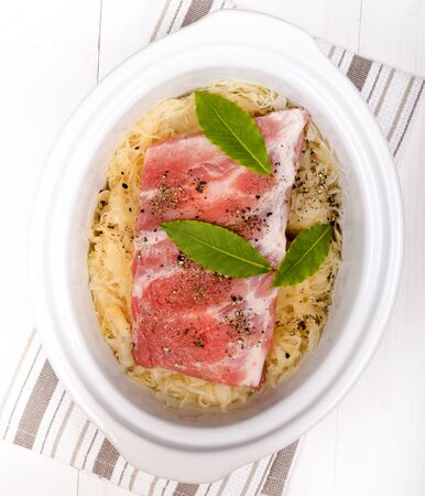 slow cooker: fresh sauerkraut and pork ribs with bay leaf in a white slow cooker