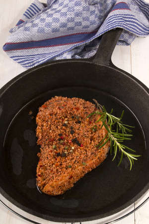 peppered: raw peppered pork chop in a cast iron pan with oil and rosemary Stock Photo