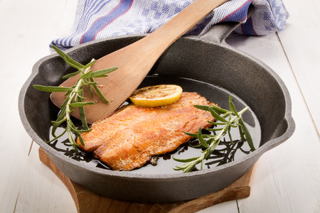 cast iron pan: grilled scottish kipper with oil and rosemary in a cast iron pan