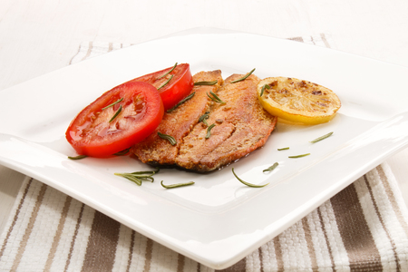 kipper: grilled scottish kipper with rosemary, tomato and slice lemon an a white plate