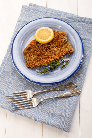 kipper: scottish with oatmeal coated kipper with thyme and slice lemon an a blue plate