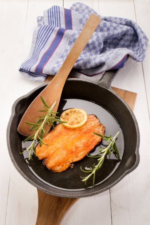 kipper: grilled scottish kipper with oil and rosemary in a cast iron pan
