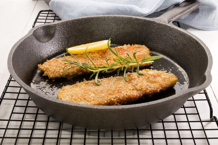 cast iron pan: grilled scottish kipper with oat bran, slice lemon, rosemary in a cast iron pan