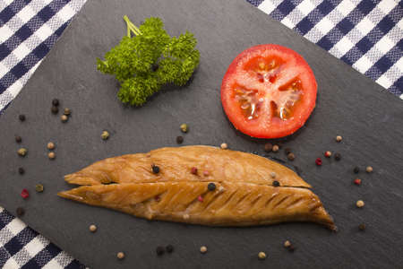 smoked: smoked mackerel with a slice tomato, parsley and mixed peppercorn on a slate plate