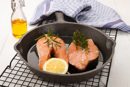 cast iron pan: raw salmon steak with lemon, thyme and rosemary in a cast iron pan