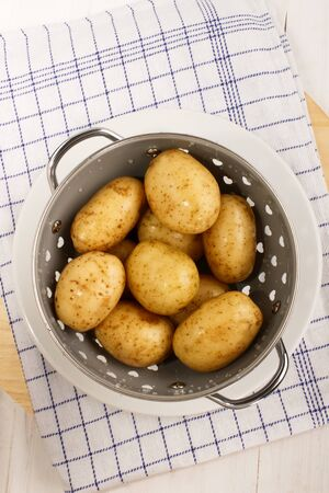 washed and wet organic potatoes in a colander