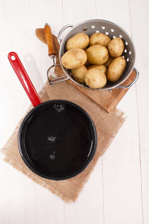 cleaned: cleaned potatoes in a colander and  enamel pot with cold water to cook the potato