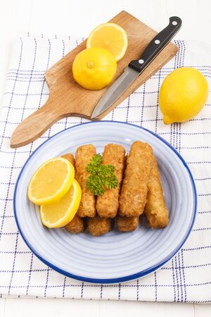 alaska pollock: deep fried fish finger made from alaska pollock fish with slice lemon and parsley on a plate Stock Photo