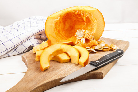 vitamin rich: raw, freshly harvested hokkaido pumpkin cut into wedges on a wooden board with kitchen knife