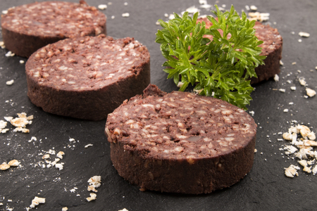 british cuisine: home made irish black pudding with oatmeal and parsley on slate