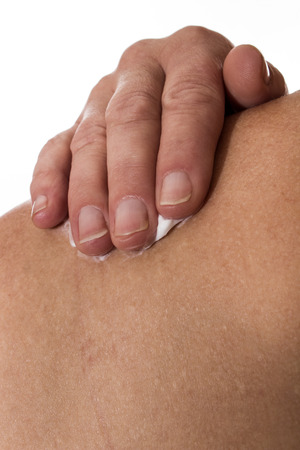 relieving pain: senior female rubbing her shoulder with a white pain relieving cream