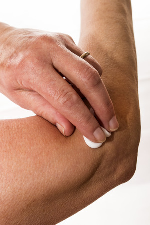 relieving pain: senior female rubbing her elbow with a white pain relieving cream