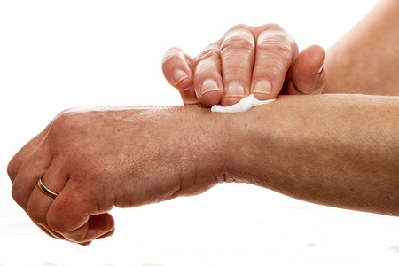 relieving pain: senior female rubbing her wrist with a white pain relieving cream