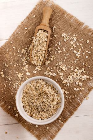 wooden scoop: organic scottish toasted oats in a bowl, wooden scoop and brown jute Stock Photo