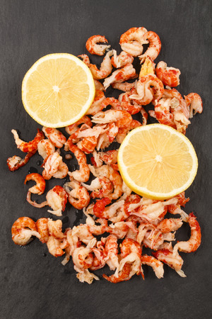 cleaned: cleaned and cooked crayfish tails with lemon slice on slate Stock Photo