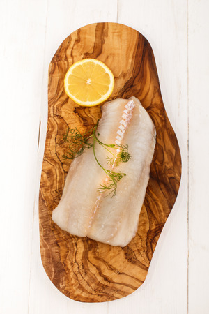 haddock: raw haddock with dill and slice lemon on a wooden board Stock Photo