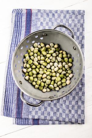 moist: moist peas in a grey metal strainer on a kitchen towel