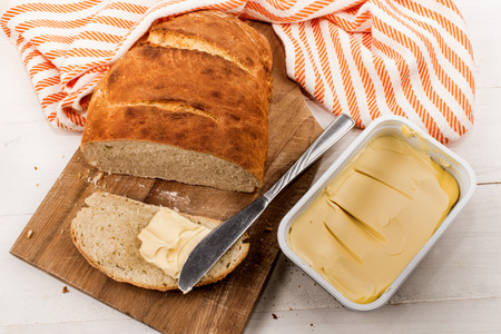 slice home baked bread with margarine and knife on a cutting board