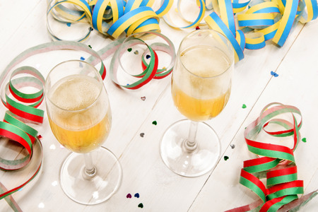 new year s eve: new year s eve party with two filled champagne glasses, colorful paper decoration and heart confetti