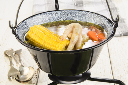 polish chicken: hungarian chicken soup with sweet corn and carrot in a black taditional kettle