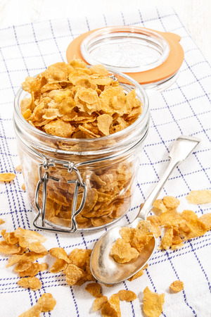 cornflakes in a glass storage container with spoon on a blue and white kitchen towel
