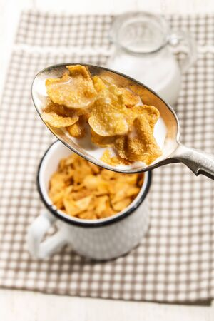 cornflakes with milk on a spoon, background enamel mug and glass with fresh and cold millk