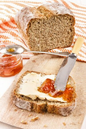 bread soda: home baked irish soda bread with butter and orange jam on a wooden board