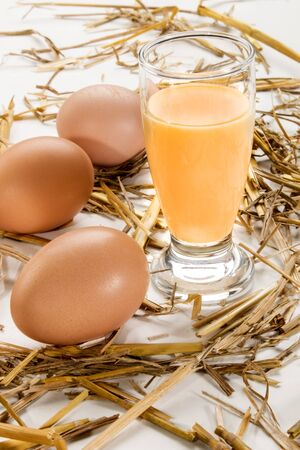 home made advocaat in a glass and eggs around with straw