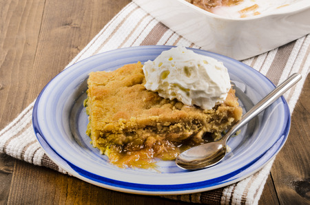 british cuisine: rhubarb crumble cake with whipped cream and spoon on a plate