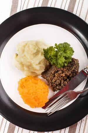 neeps: typical scottish dish, haggis with mashed potato, turnip and parsley on a plate