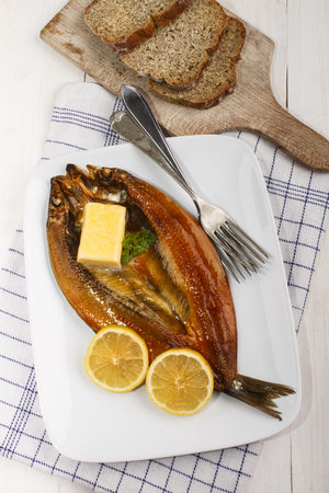 scottish smoked kipper with lemon, butter and parsley on a plate