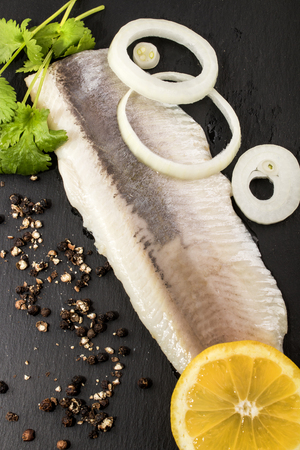 marinated herring with onion,  lemon, crushed black peppercorn and coriander on slate