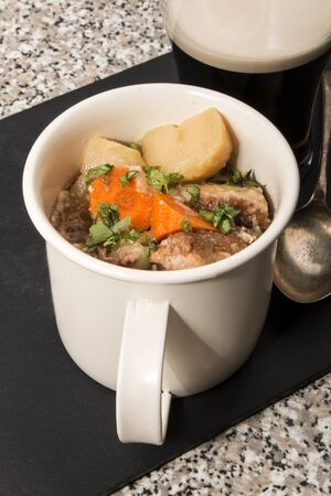 dublin coddle, an irish specialty in a mug on slate