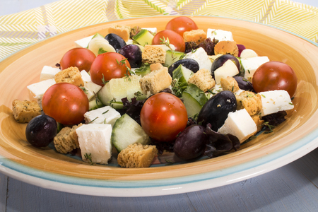 mediterranean salat with black olive, grape, goat cheese and croutons on a plate