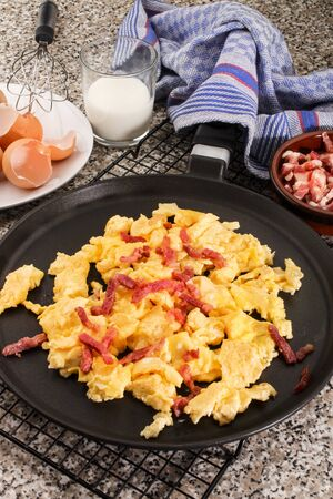 warm scrambled eggs with fried bacon bits in a pan Stock Photo