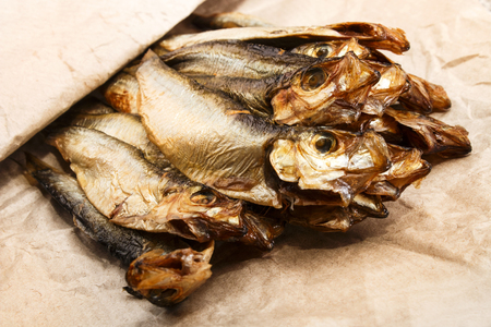fresh smoked sprats in a brown paper bag