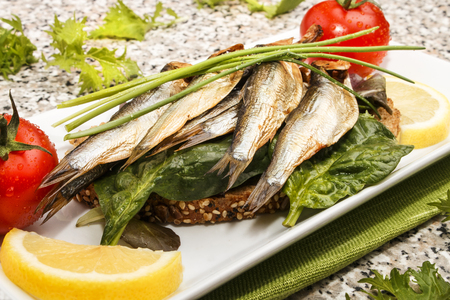 smoked sprats with salad on a slice of bread as well as lemon, tomato and chives on a plate